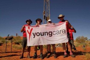Four Suncorp trekkers at geo centre holding Youngcare flag