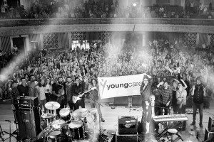 Bands-of-the-Youngcare-Benefit-Concert-holding-a-Youngcare-flag-in-front-of-the-crowd